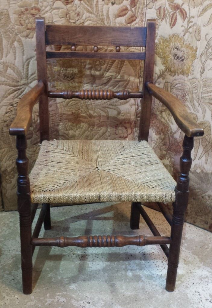 Antique country armchair with rush seat.
