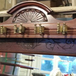 A mahogany Edwardian cue rack, with carving detail and mirror.
